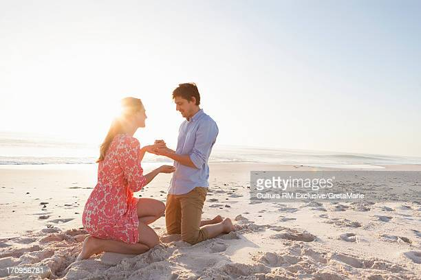 Man proposing to woman on beach
