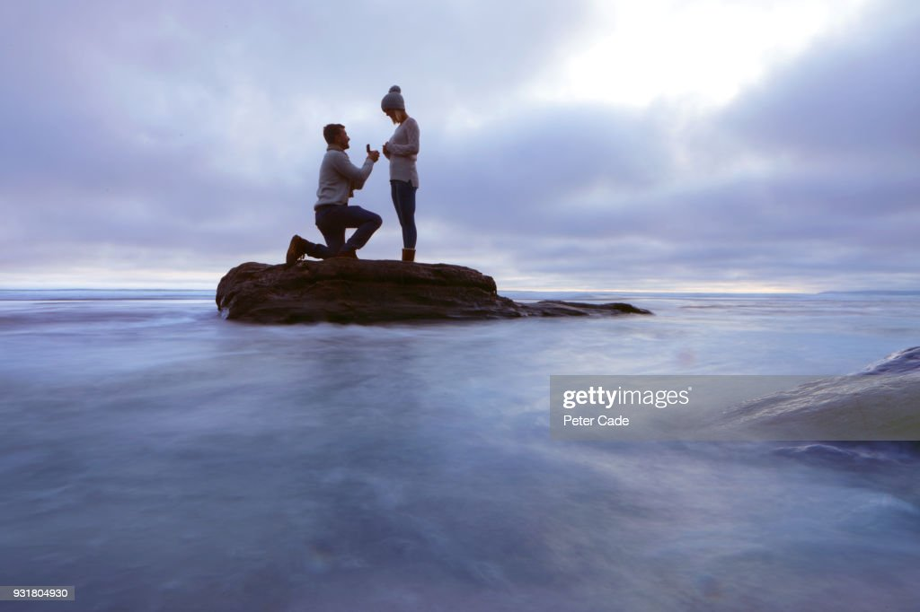 Man proposing to woman on rock in sea : Stock Photo