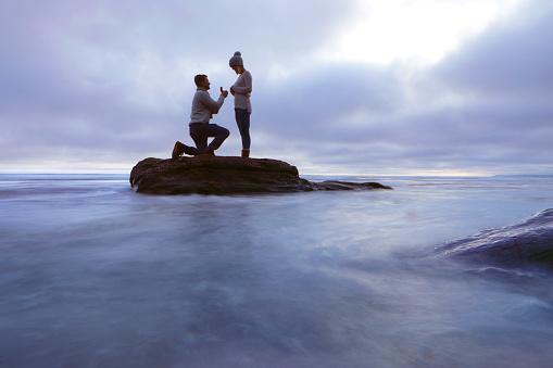Man proposing to woman on rock in sea - gettyimageskorea