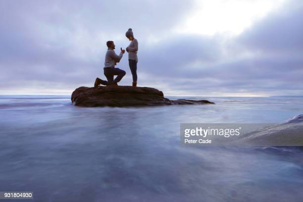 man proposing to woman on rock in sea - fidanzato foto e immagini stock