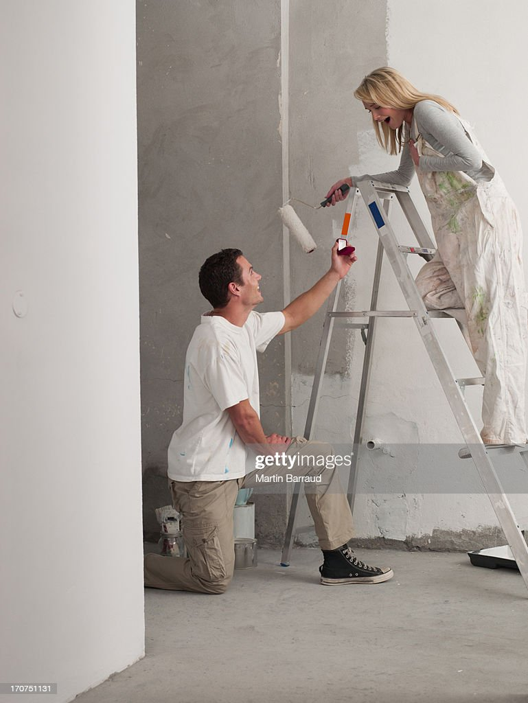 Man proposing to woman painting wall : Stock Photo