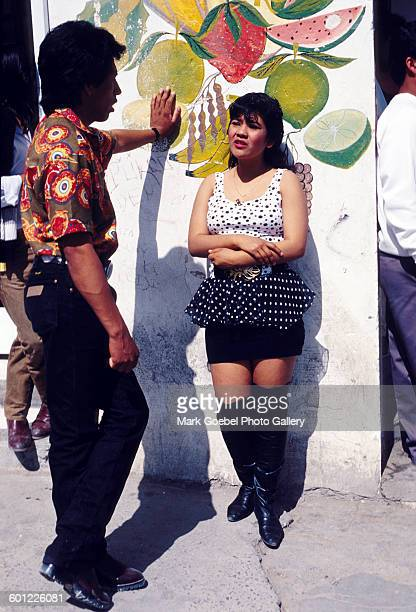 A man propositions a female prostitute in front of a wall decorated with an illustration of fruit Juarez Mexico late 1980s