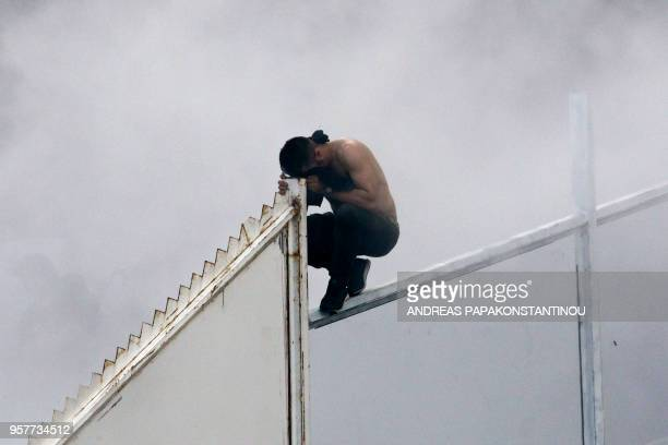 A man protects himself from smoke as fans light flares ahead of the Greek Cup Final football match between AEK FC and PAOK Salonika at the Olympic...