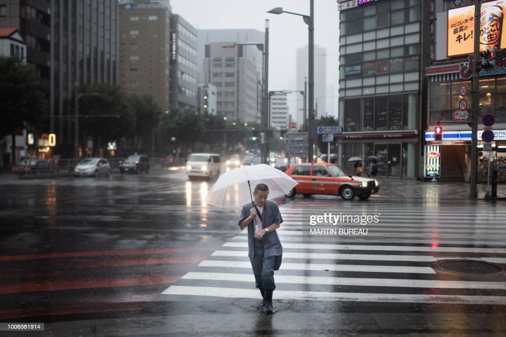 A man protects himself from the rain with an umbrella in Tokyo on