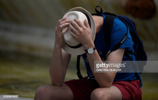 A man protects himself from the sun with a hat on a hot summer day in Sevilla on August 1 2018 as a heatwave hits Spain and Portugal