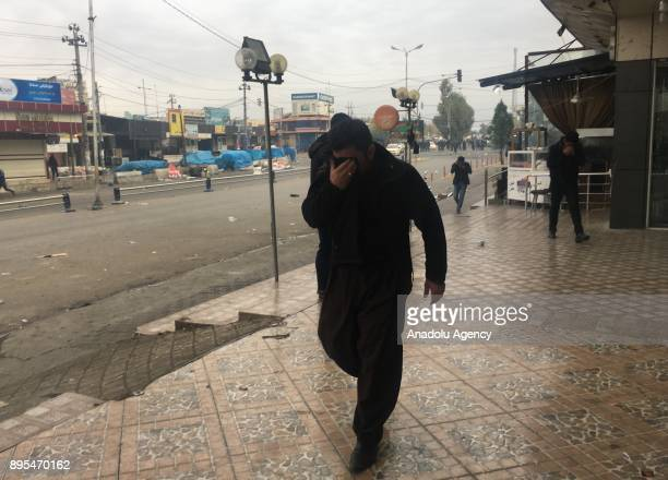 A man protects his face from tear gas during the antigovernment protests in Sulaymaniyah in Sulaymaniyah Iraq on December 19 2017