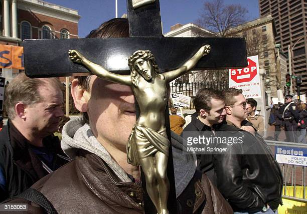 A man protesting against gay marriage holds a crucifix as two progay marriage protesters embrace outside the Massachusetts State House March 29 2004...