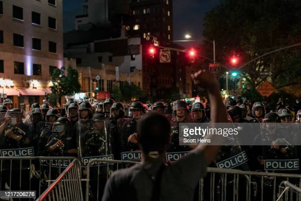 Man protesting police brutality and systemic racism holds up his hand as demonstrators are kept in place on the Manhattan Bridge by police for hours...