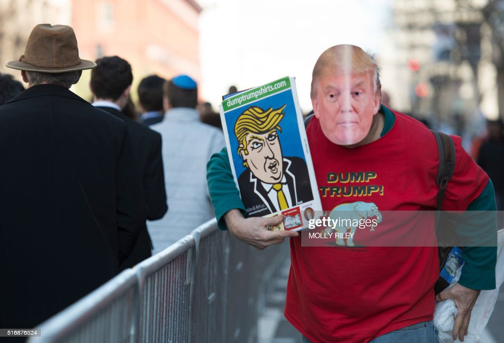 A man protesting US Republican presidenial candidate Donald Trump walks next to the line of attendees entering Verizon Center during the AIPAC 2016 Policy Conference on March 21, 2016 in Washington, DC. Trump and other presidential primary candidates are speaking at the event.