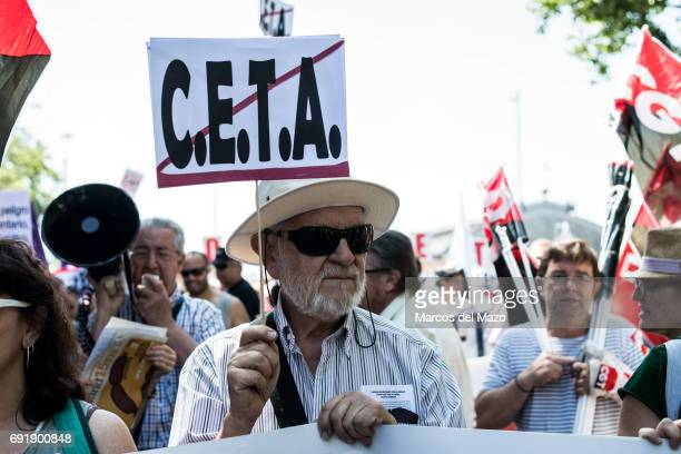 A man protesting with a placard against CETA trade deal during a demonstration demanding Spanish government not to ratify trade agreement between...