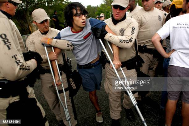 A man protests as he is carried away by members of the Florida Highway Patrol from the entrance to a planned speech by white nationalist Richard...