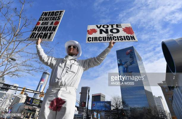 A man protests circumcision outside the Super Bowl Experience in Atlanta Georgia on February 2 2019 The New England Patriots will meet the Los...