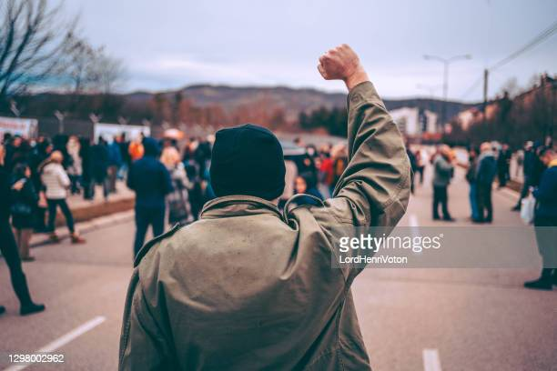 man protests in the street with raised fist - social justice concept stock pictures, royalty-free photos & images