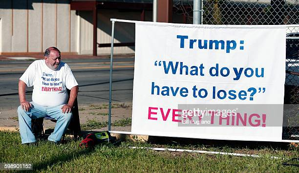 A man protests Republican Presidential Nominee Donald Trump's visit to Great Faith International Ministries Church September 3 2016 in Detroit...