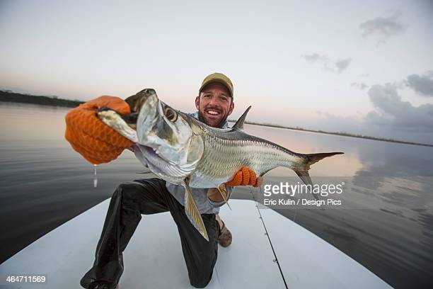 a man proudly holds a large fresh caught fish on the stern of a boat - big fish stock pictures, royalty-free photos & images