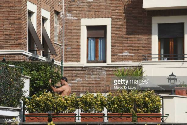A man prunes plants on his terrace on March 22 2020 in Rome Italy As Italy extends its nationwide lockdown to control the spread of COVID19 its...