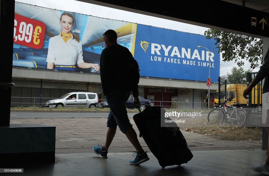 A man pulling a suitcase walks past a billboard advertisement for RyanAir during a 24-hour strike by RyanAir pilots on August 10, 2018 in Schoenefeld, Germany. RyanAir pilots in Germany, Ireland, Sweden, Belgium and Holland are taking part in the strike over demands for better pay and working conditions.