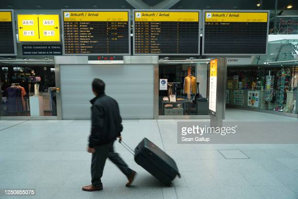 Man pulling a suitcase walks past a flight arrivals board that shows only a fraction of flights compared to before the pandemic at Tegel Airport...