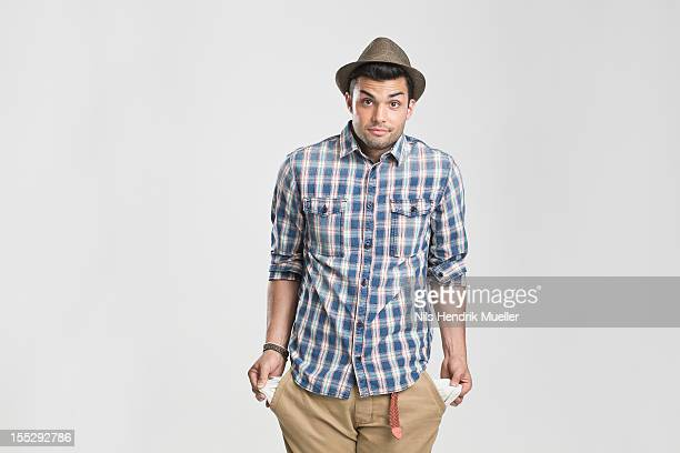 man pulling at empty pockets - pocket stock photos and pictures