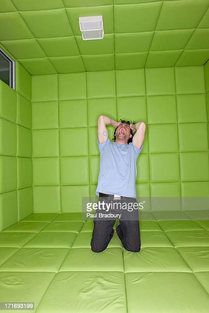 man pulling at hair and screaming in padded room - insanity stock pictures, royalty-free photos & images