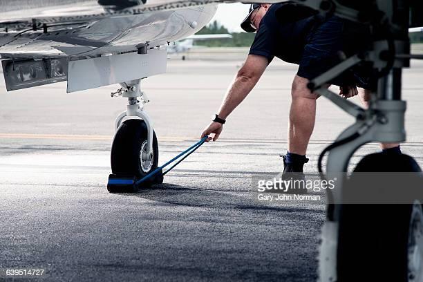 Man pulling blocks away from airplane wheel