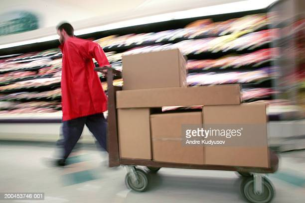 Man pulling cart with boxes in grocery store