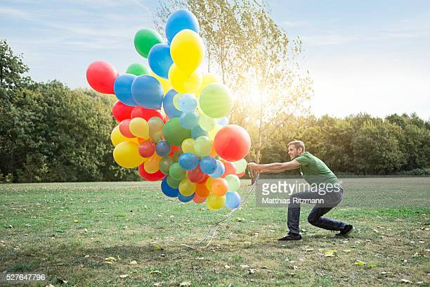 Man pulling colorful balloons