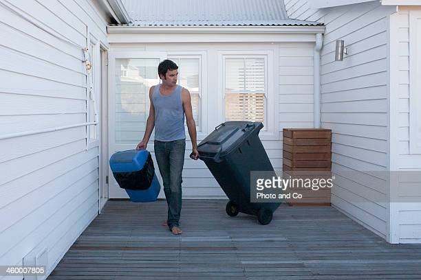 Man pulling garbage can