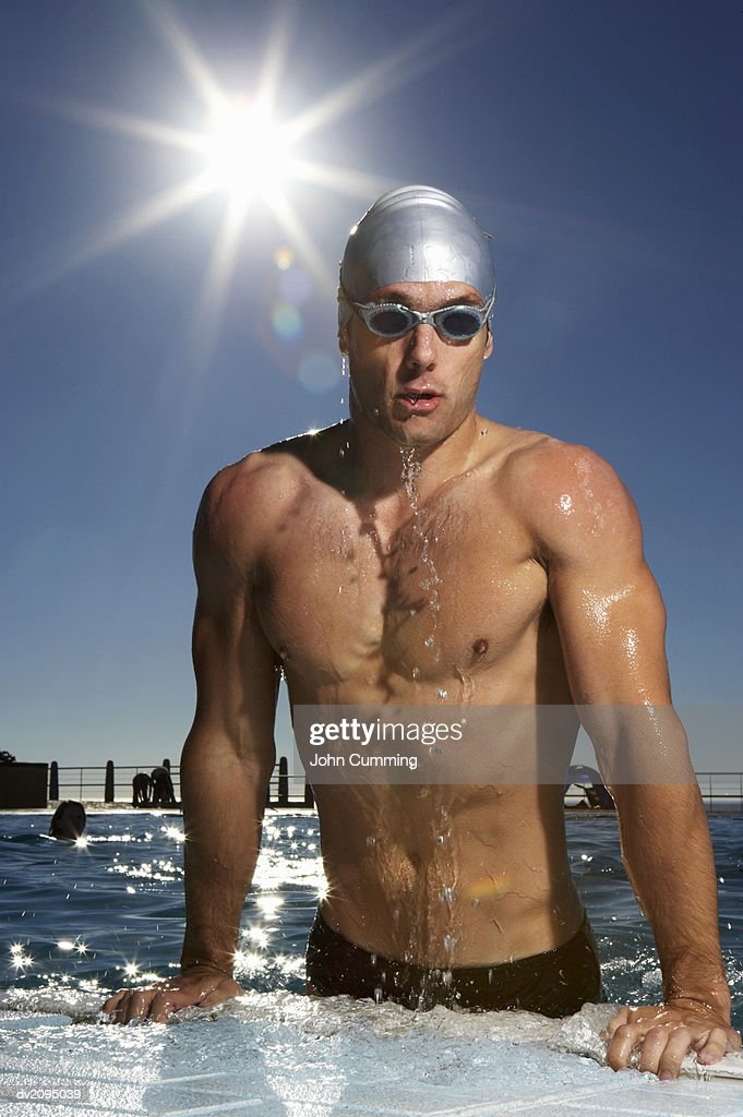 Man Pulling Himself Out of a Swimming Pool : Stock Photo
