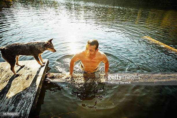 Man pulling himself out of water onto log