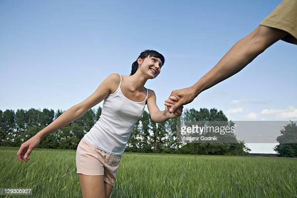 A man pulling his girlfriend through a field