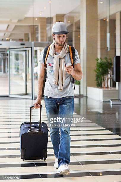 Man pulling his luggage at an airport and using a mobile phone