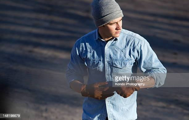 Man pulling off gloves outdoors
