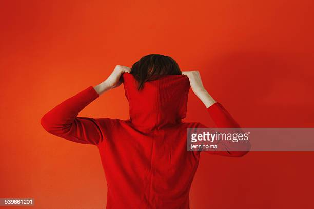 man pulling red sweater over face against red background - escondendo - fotografias e filmes do acervo