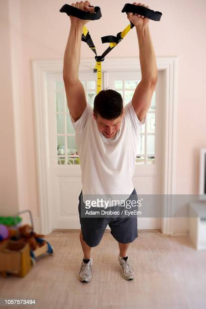 man pulling resistance band at home - the doors band stock pictures, royalty-free photos & images