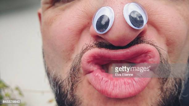 Man pulling silly face with Googly eyes on nose