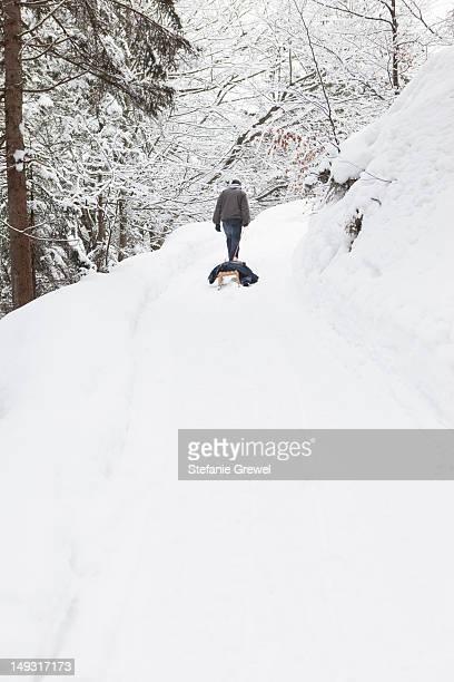man pulling sled in snowy field - stefanie grewel stock-fotos und bilder