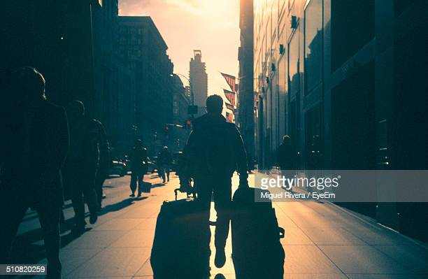Man pulling suitcases on street