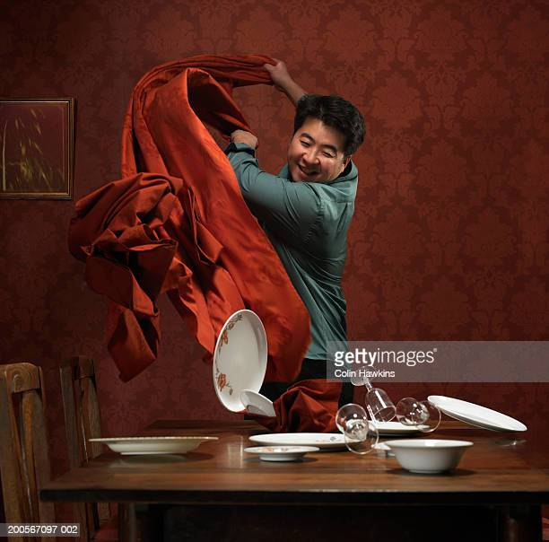Man pulling tablecloth off table, plates and glasses falling over
