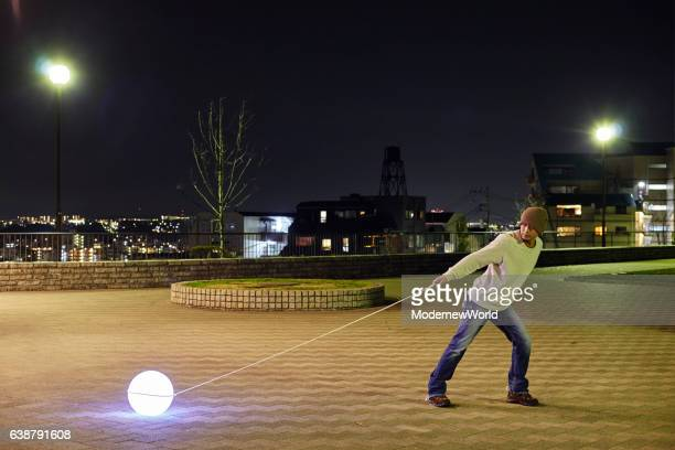 A man pulling the rope of the Led ball #01