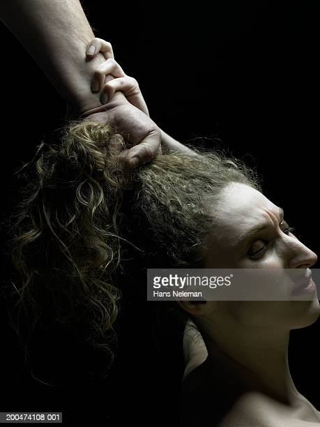 Man pulling young woman by hair, close-up