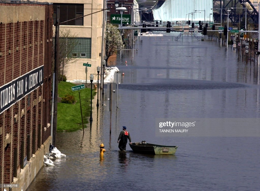 A man pulls a boat down flooded River Road 25 Apri : News Photo