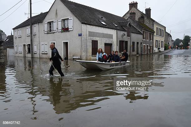 A man pulls a boat of residents through a flooded street in Nemours southeast of Paris on June 1 2016 Torrential downpours have lashed parts of...