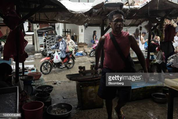 A man pulls a box containing goods as people purchase groceries at a market ahead of Typhoon Mangkhut's arrival in Tuguegarao Cagayan province the...