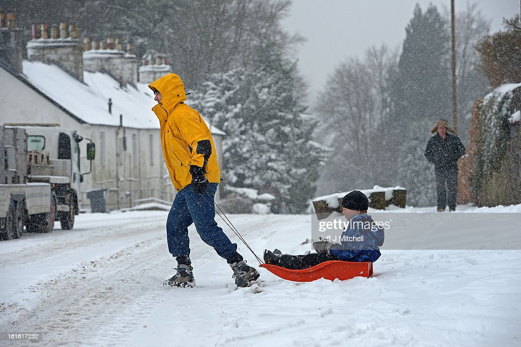 KINGDOM - FEBRUARY 13 A man pulls a boy on a sledge during recent snowfall on February 13, 2013 in Blanefield, Scotland. Weather forecaster have issued a yellow weather warning of up to 10cm of snow on higher routes, with the possibility of travel disruption.