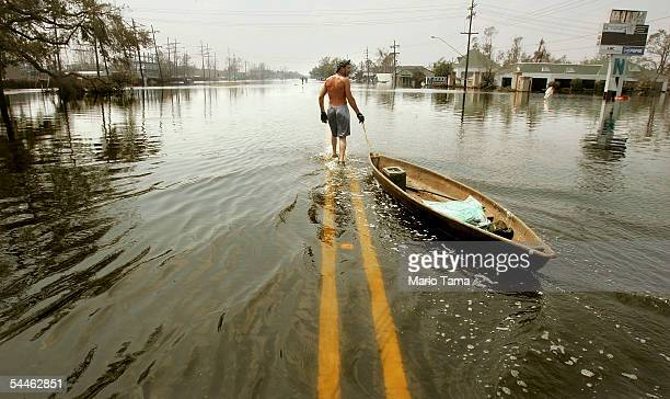 A man pulls a canoe down a flooded street in the hardhit Chalmette community of Saint Bernard's Parish September 3 2005 in New Orleans Today was the...