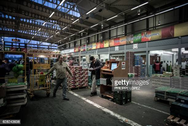 A man pulls a cart at the fruits and vegetables pavilion of the Rungis international food market in Rungis a southern suburb of Paris on December 7...