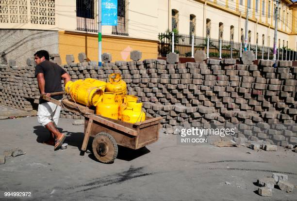 A man pulls a cart with gas cylinders next to a barricade in Masaya Nicaragua on July 4 2018 Nicaragua is reliving the horror of the 1970's and the...