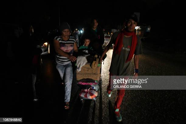 A man pulls a child in a shopping cart as Honduran migrants part of the second caravan to the United States leave San Pedro Sula 180 km north of...