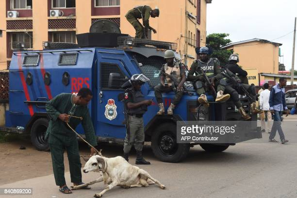 A man pulls a ram as Nigerian police officers take position outside a courtroom after a suspected kidnap kingpin was arraigned at the Lagos State...